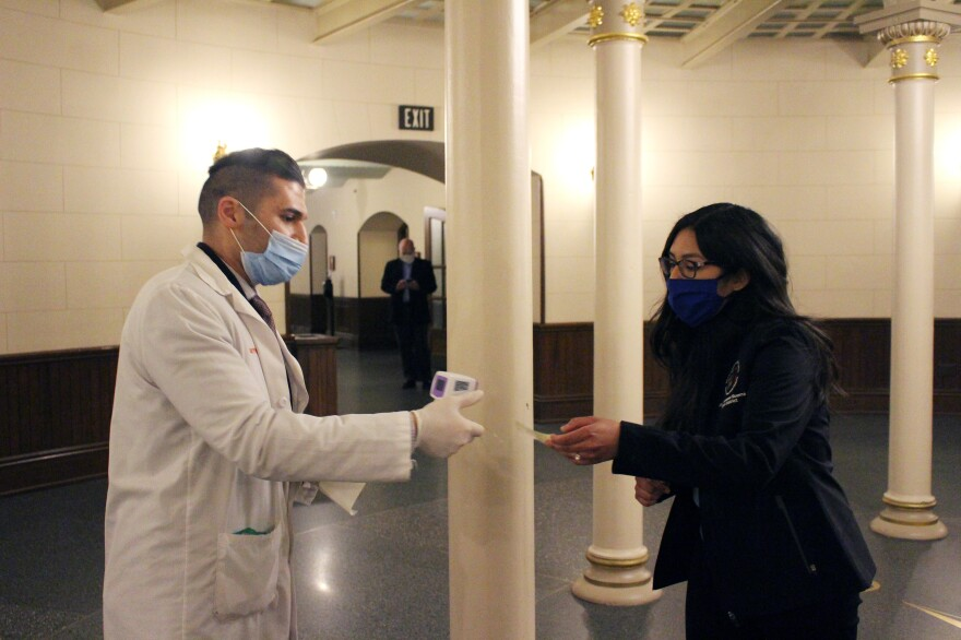 Alex Mchawrab, a pharmacist deputized to take the temperatures of lawmakers as they entered session Tuesday, takes a sticker allowing reentry from Democratic Rep. Vanessa Guerra. After lawmakers checked in for session, they were encouraged to leave before returning hours later for a voice vote.