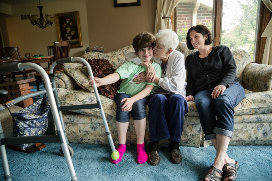 Three generations: Zoe, 8, Evelyn, and Nancy, sit on the couch of their living room. Dan says the children love having their grandmother live with them.