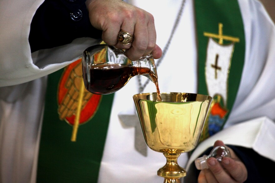 Priest pours wine into a chalice