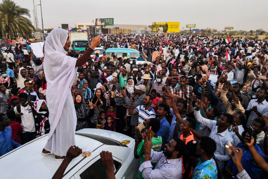"Standing on a white car and wearing a traditional white thobe, Sudanese student Alaa Salah led protest chants against longtime dictator President Omar al-Bashir in Khartoum in April 2019. A social media post showing a photo of Salah went viral, and she was dubbed Sudan's ""Lady Liberty."" Sudan's military ousted Bashir that same month."
