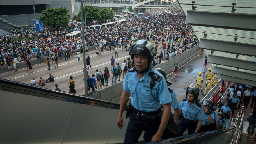 Police officers walk up an escalator after demonstrators storm onto a highway during ongoing pro-democracy protests in Hong Kong Sunday.