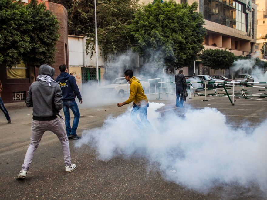 Anti-military protesters run away from tear gas fired by riot police near the Ramsis square, downtown Cairo, Egypt, on Saturday.