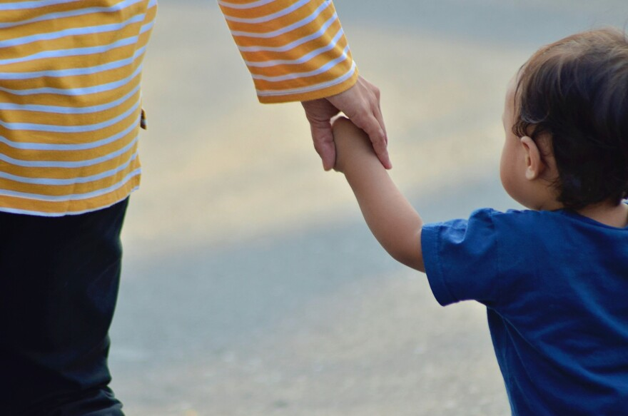 Photo of young Child & Mom holding hands.