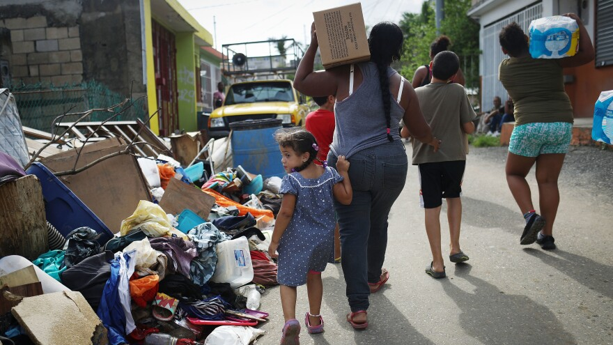 Residents of San Isidro, Puerto Rico, carry food and water provided by FEMA to a neighborhood without electricity or running water last October.