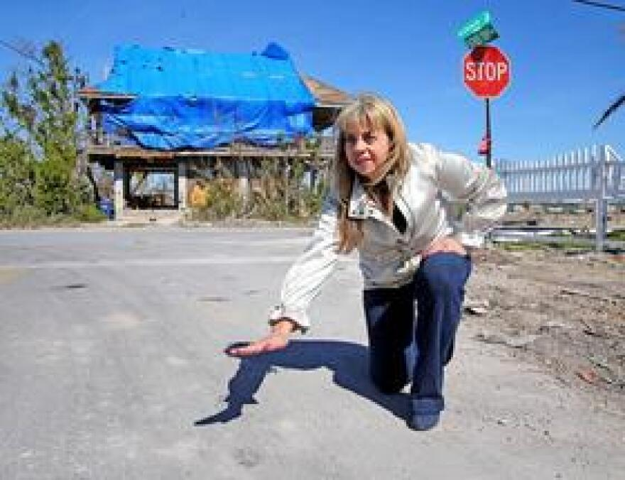 """Rhonda Haag, manager of Monroe County's sustainability program, demonstrates how high water reached after Hurricane Irma. Roughly half of the county's roads are susceptible to sea-level rise flooding in the next 20 years, and officials have begun a program to raise some of the roads six to 12 inches. Elevating any higher than that -- """"Well, that's expensive,"""" Haag told the Miami Herald."""