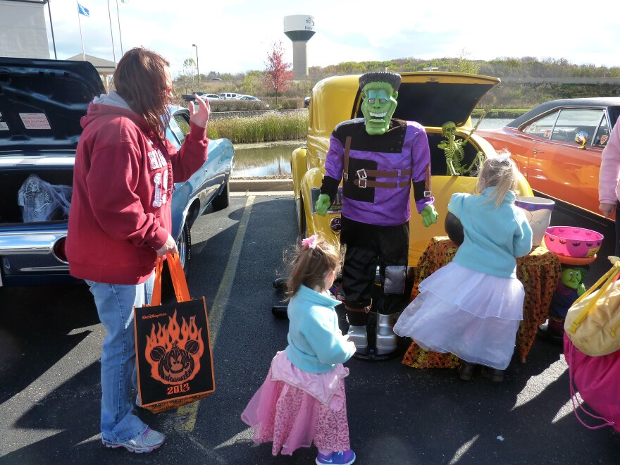 "A family plucks candy from one of the cars at the ""trunk or treat"" event in New Berlin, Wis."