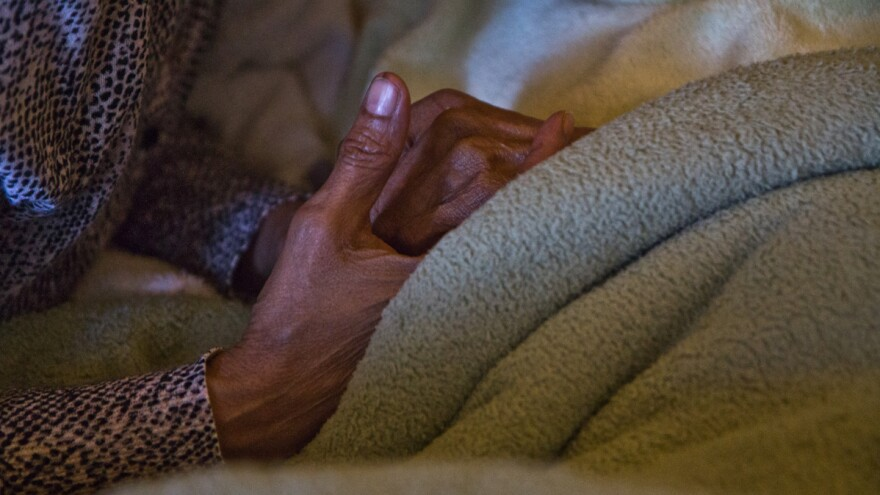 Angela Bobo holds the hand of her mother, Ruth Perez. Bobo is Perez's at-home caregiver.