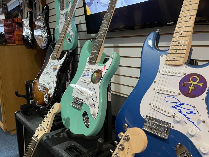 Tres guitarras firmadas se sientan encima de los amplificadores.