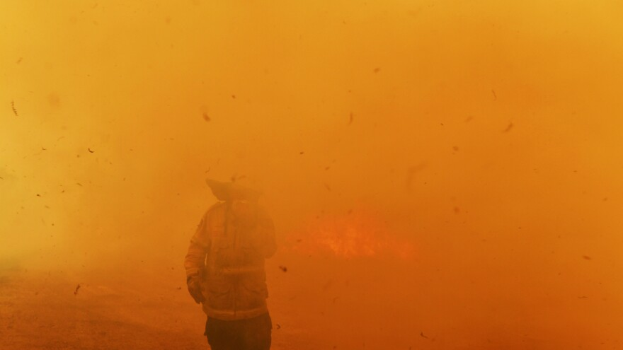 A firefighter walks through the haze produced by a wildfire racing through Hillville, Australia, earlier this month.