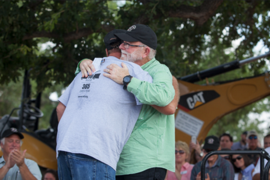 Ellis Johnston hugs Mobile Loaves & Fishes founder and president Alan Graham at the ground-breaking ceremony of tiny home village in 2014.