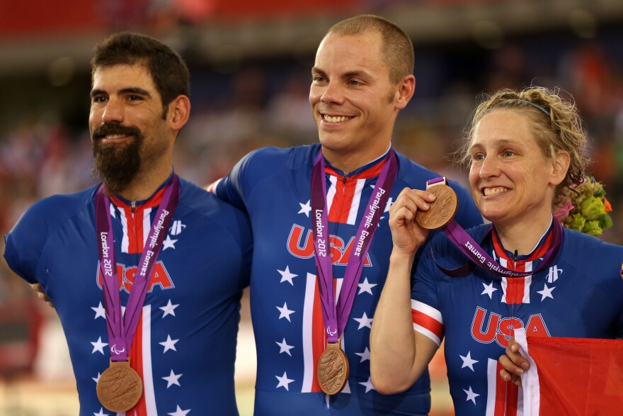 Bronze medalists Jennifer Schuble (right), Sam Kavanagh (center) and Joseph Berenyi of the United States stand on the podium for the Mixed C1 to 5 cycling team sprint finals at the 2012 Paralympic Games in London.