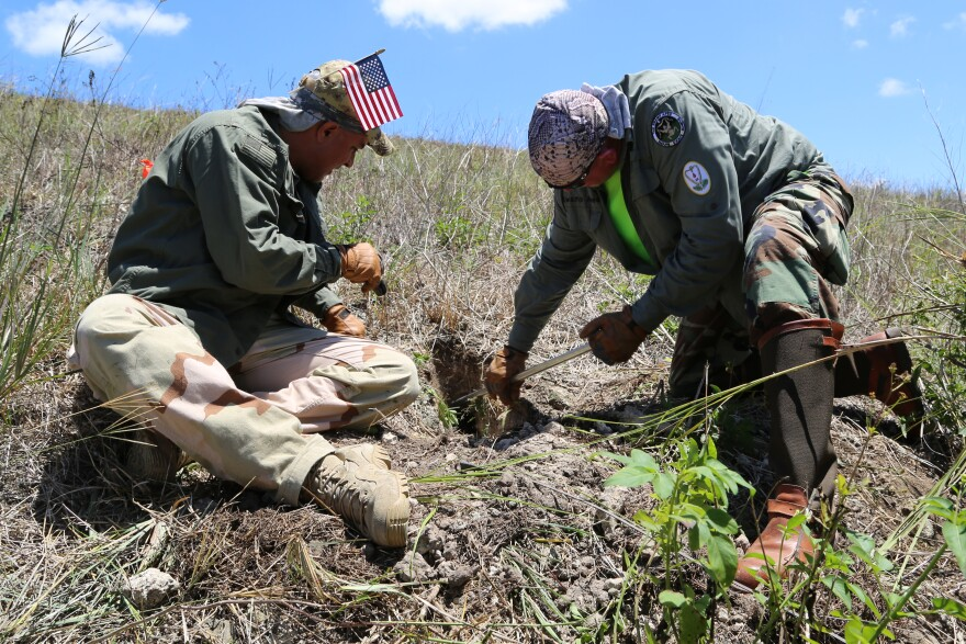 Swamp Apes Joe 'Mojo' Detre and Tom Aycock dig a hole on the side of a levee looking for Burmese python nests.