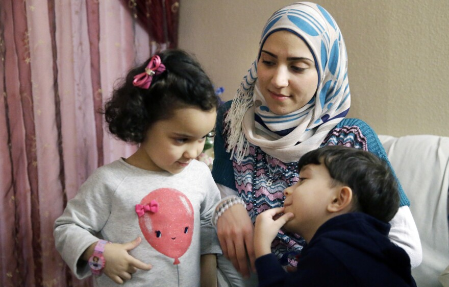 Syrian refugee Maryam al-Jaddou sits with her children Maria (left) and Hasan in their apartment in Dallas. Jaddou says she decided to leave Syria in 2012 after her family's home in Homs was bombed and there was nowhere safe left to live.