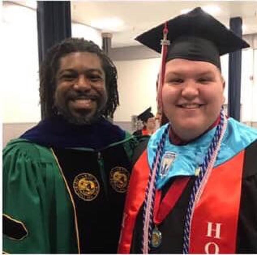 Dr. Graham and Sam Estes smiling in graduation garb.