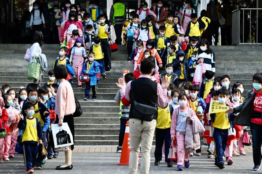 Children wearing face masks leave their elementary school at the end of the day in Xindian district, New Taipei City, on March 3.