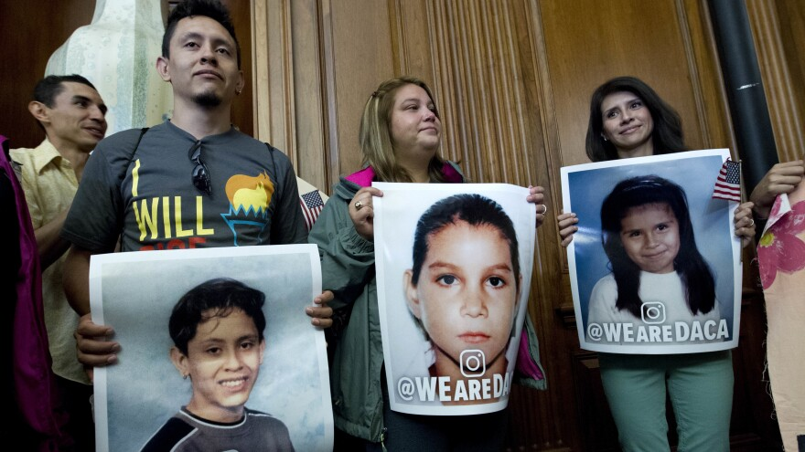 DREAMers from left: Isaac Montiel, 28, of New York City; Monica Camacho, 23, of Bethesda, Md.; and Cynthia Toyco, 33, of Rogers, Ark., hold their pictures, during the House and Senate Democrats, news conference on Capitol Hill on Sept. 6, 2017.