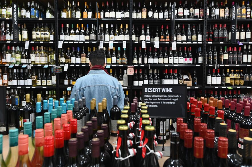 A patron stands in front of a shelf full of wine bottles at a liquor story in the Brooklyn borough of New York City on March 20.