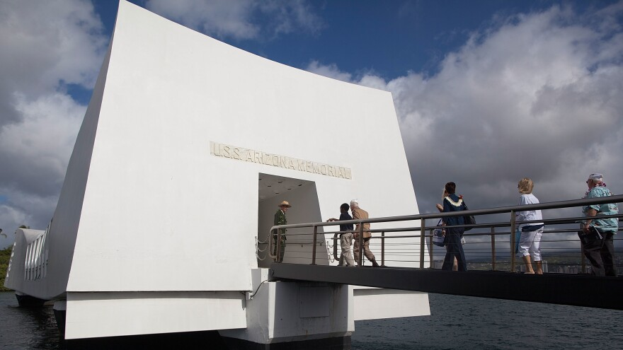 People enter the <em>Arizona</em> Memorial during a memorial service for the 70th anniversary of the attack on the U.S. naval base at Pearl Harbor.