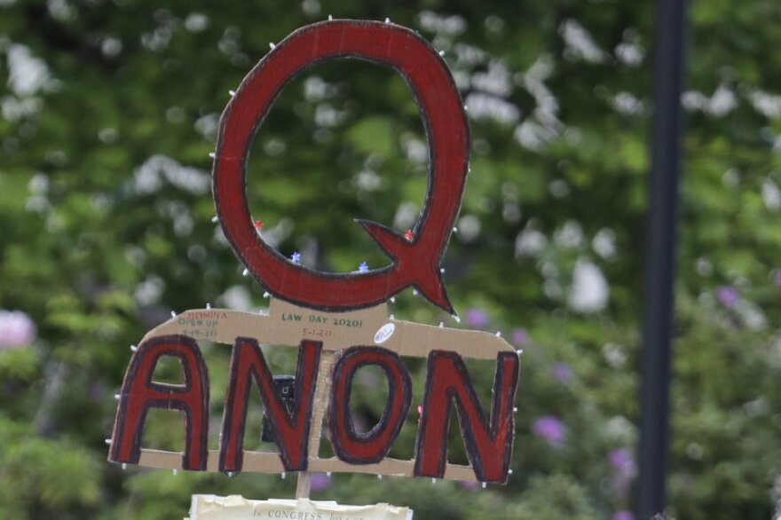A handmade QAnon sign, red letters outlined in black, is seen at a protest rally in Olympia, Washington, in May 2020.