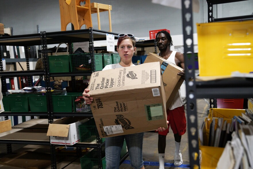 Melissa Badeker and a Maryland Book Bank staff member carry donations through the warehouse.