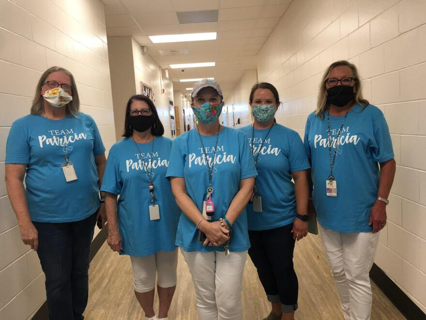 Five women in a school hallway wearing face masks and teal shirts with Team Patricia printed on them