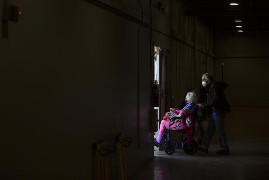 Senior being pushed in a wheel chair at Dallas' Fair Park vaccine site.