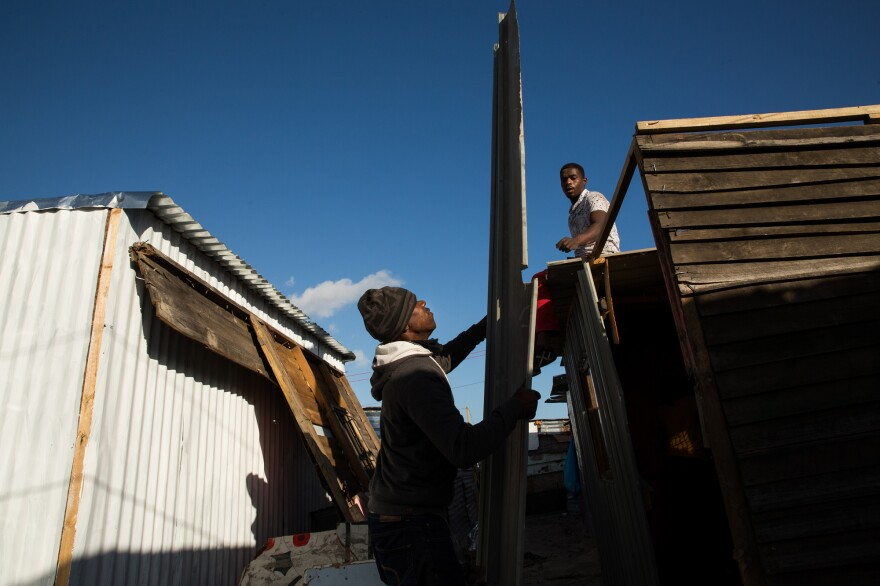 """Two men help Noxolo Nondala build her home in Covid. She previously lived in the township of Khayalitsha, where she had been a backyard dweller, renting a structure that was literally in someone's backyard. Although she liked her life in Khayalitsha, she said she moved to Covid """"because it had more space. And for now, in COVID times, that was more important. This is my best option for now."""""""