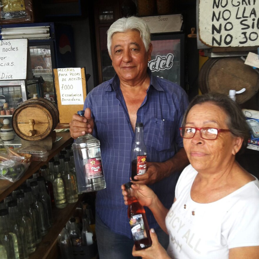 Mareya Evies, a cocuy shop proprietor in Barquisimeto, and her husband hold bottles of the beverage, which is sometimes infused with fruit and mixed with juice.