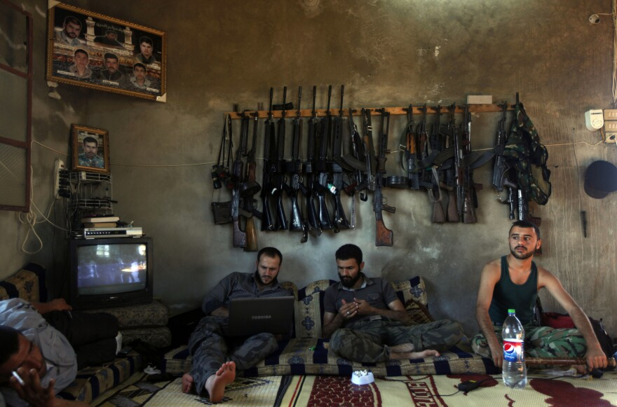 Free Syrian Army fighters sit in a house on the outskirts of Aleppo, Syria, in June 2012. The U.S. is planning to train and arm the rebels, who have been outgunned on the battlefield.