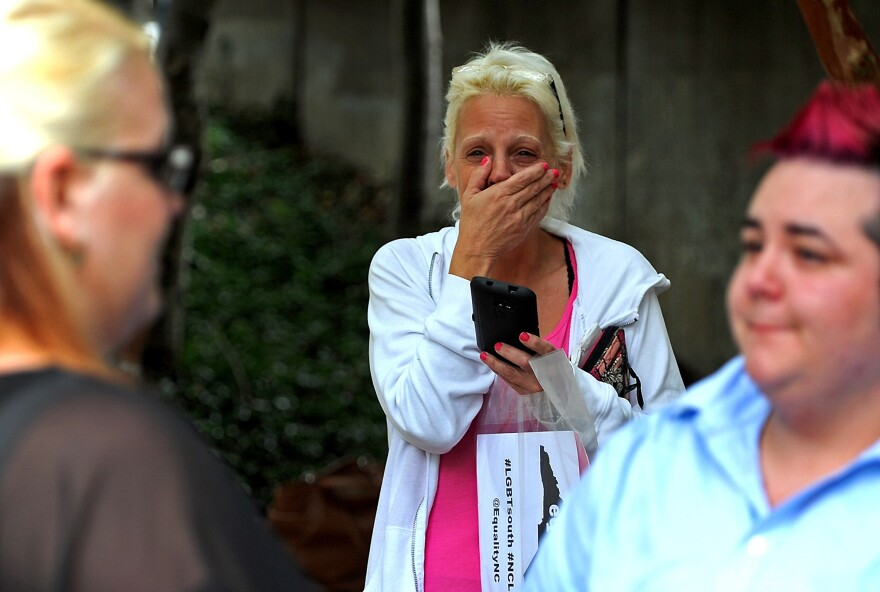 Lynda Johnson (center) cries as she watches her daughter Kandyce Johnson (left) marry Jana Downs in Charlotte, N.C., on Monday. Same-sex couples lined up to get marriage licenses Monday, the first day Mecklenburg County issued the licenses.