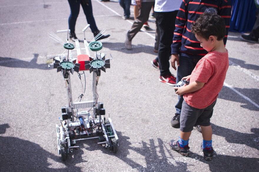 A young maker controls a robot on the sidewalk at the 2014 World Maker Faire in Queens, NY.