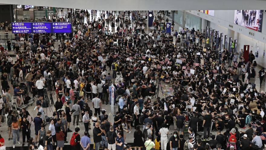 Demonstrators gather during a protest at Hong Kong International Airport, Friday, with the goal of alerting travelers to their call for democratic reforms and the withdrawal of a controversial extradition bill.