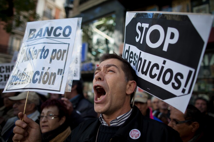 """A demonstrator shouts during a protest against housing evictions in Madrid last month. The sign to his right reads, """"Stop evictions."""""""