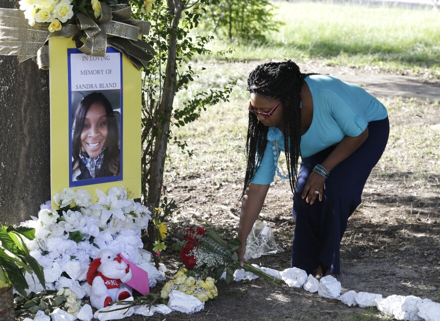 In this July 21, 2015 file photo, Jeanette Williams places a bouquet of roses at a memorial for Sandra Bland near Prairie View A&M University, in Prairie View, Texas.