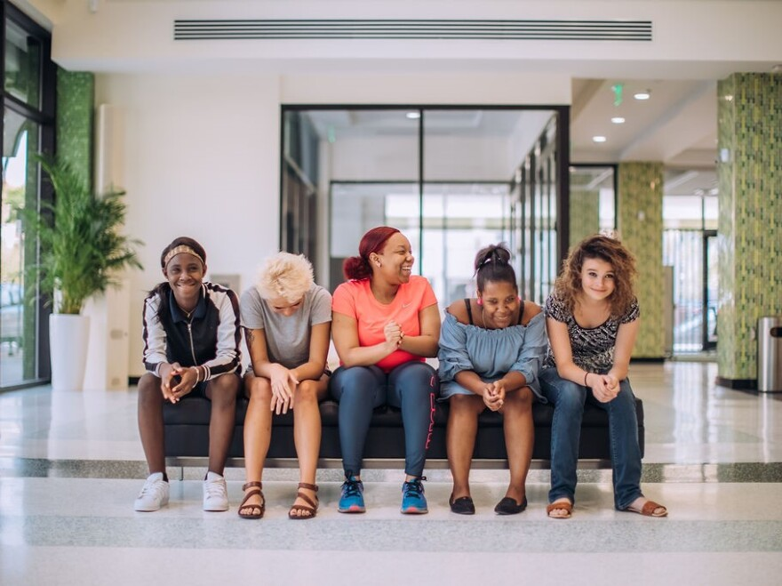 A group of girls of all different races sitting in the lobby of an office building.