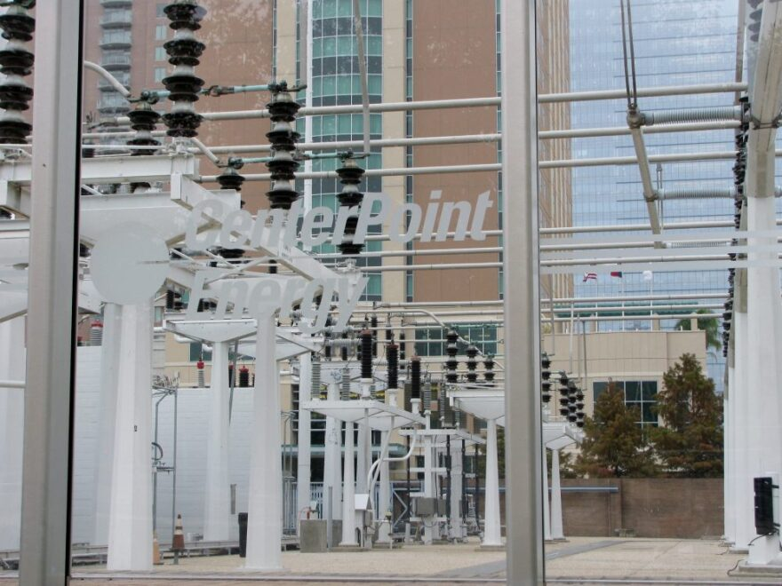 """A group of power transmission lines at a power plant. A sign at the front says """"CenterPoint Energy."""""""
