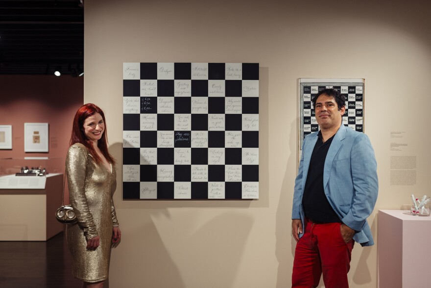 """Jennifer Shahade and Daniel Meirom flank their creation at the debut of the """"A Beautiful Game"""" exhibit at the World Chess Hall of Fame on Oct. 10, 2019."""