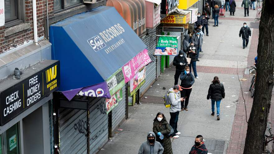 In the Queens borough of New York City on Tuesday, people wearing face masks wait in line to enter a store that offers check-cashing services.