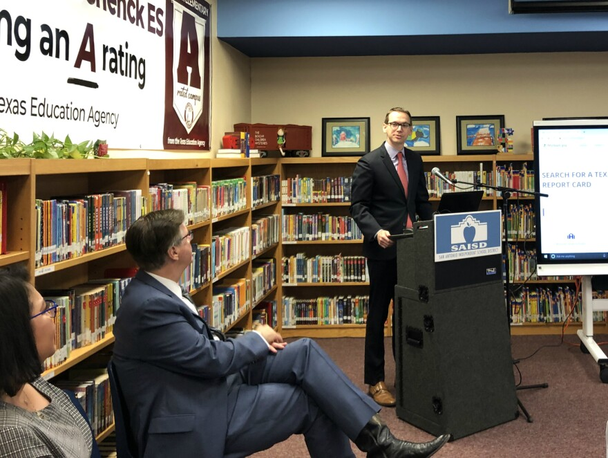 Texas Education Commissioner Mike Morath praises Schenck Elementary for moving from a C to an A rating on the state's accountability rating Aug. 15, 2019 as Texas Lt. Gov. Dan Patrick and SAISD board trustee Debra Guerrero look on.