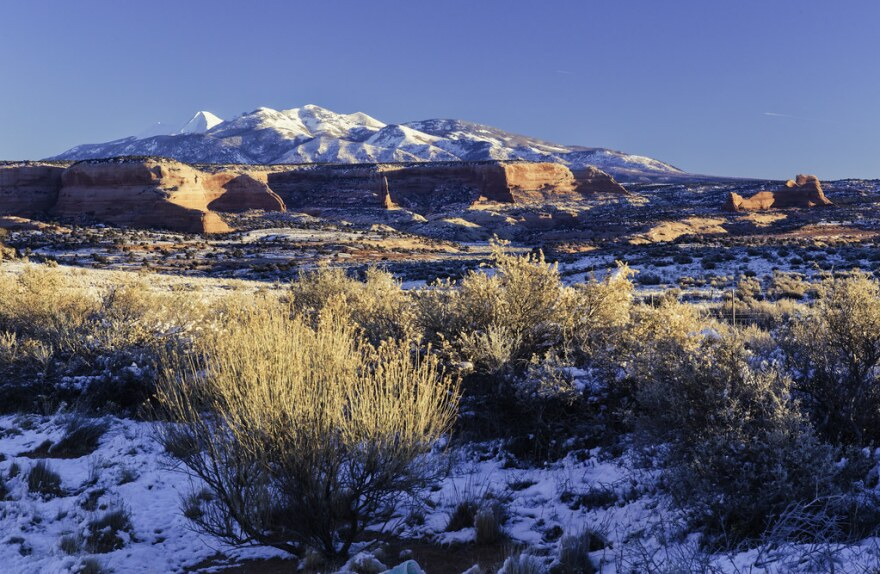 A red rock bench in the foreground with snow-covered mountains in the background.