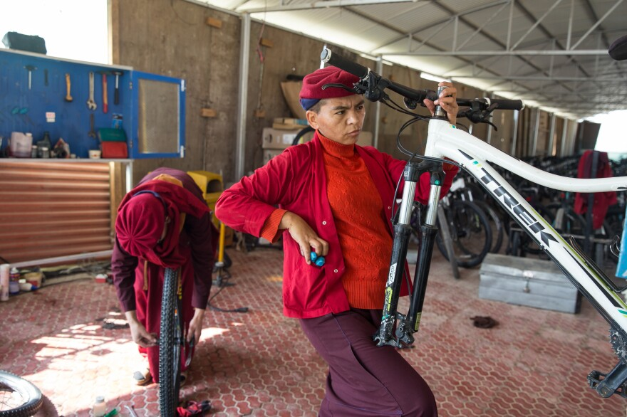 Jigme Kunga Lhamo repairs a bicycle. She is one of the main mechanics on the 2,500-mile bicycle trip the nuns take to educate villagers about the dangers of trafficking.