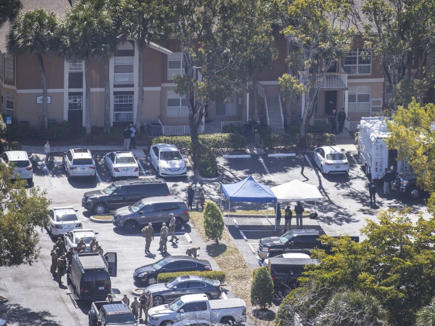 The FBI says Special Agent Daniel Alfin and Special Agent Laura Schwartzenberger died during a raid that was part of an investigation into violent crimes against children. Here, law enforcement officers investigate the scene of the raid in an apartment complex in Sunrise, Fla.