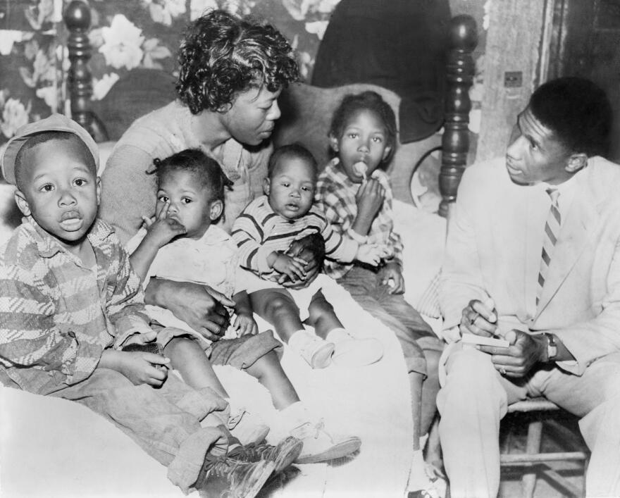 Beulah Melton, widow of Clinton Melton, speaks with NAACP field secretary Medgar Evers in 1955. She holds her four children including 5-year-old Deloris (right).