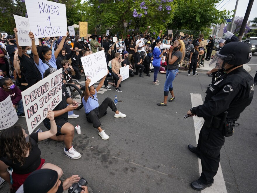 Demonstrators kneel when they are redirected by police officers on Monday in the Hollywood area of Los Angeles.