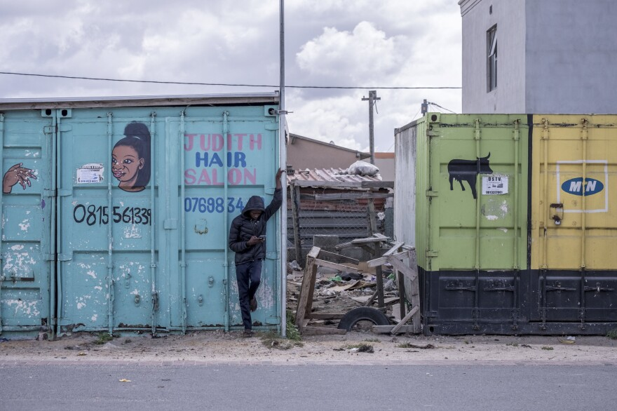 A boy checks his phone outside a shuttered hair salon in the township of Khayelitsha.