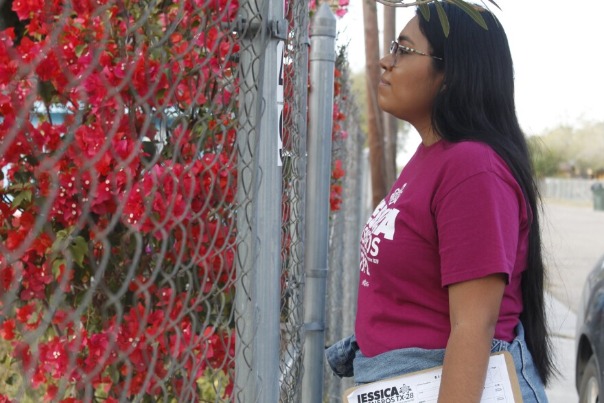 Jessica Cisneros looks through a chain link fence while knocking doors.