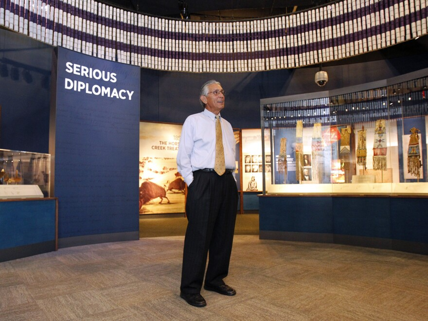 """Kevin Gover, director of the National Museum of the American Indian, stands inside the """"Nation to Nation"""" exhibit."""