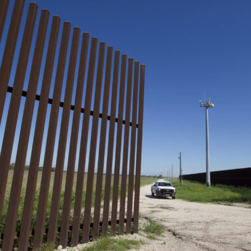 A portion of the south Texas border fence and remote surveillance cameras.