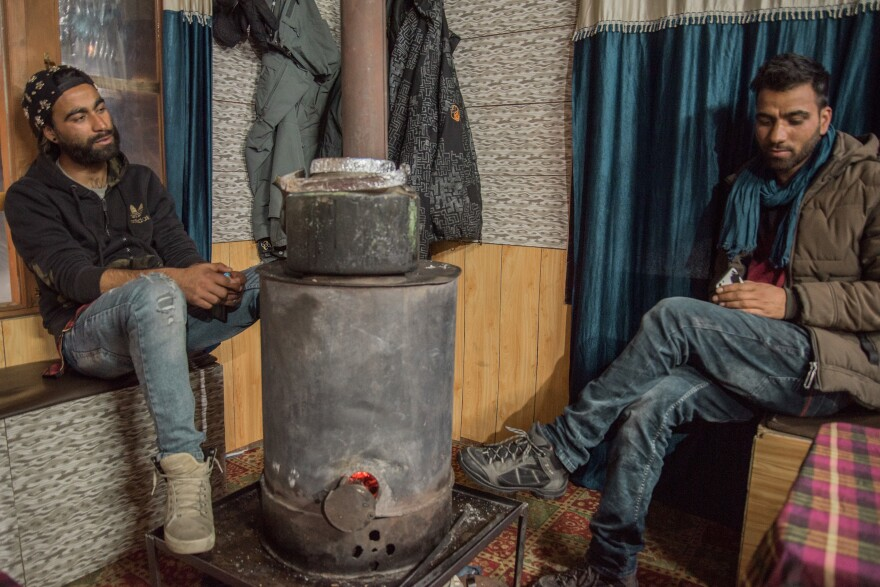 Raja Wasim Khan (left), 24, and his brother Ashraf Khan, 21, huddle around a wood stove inside the ski hut they manage in Gulmarg. The Khan brothers' father was a Kashmiri militant who served time in an Indian prison and then moved his sons to the mountains and taught them snowboarding. He wanted to keep them away from the violence he grew up in.