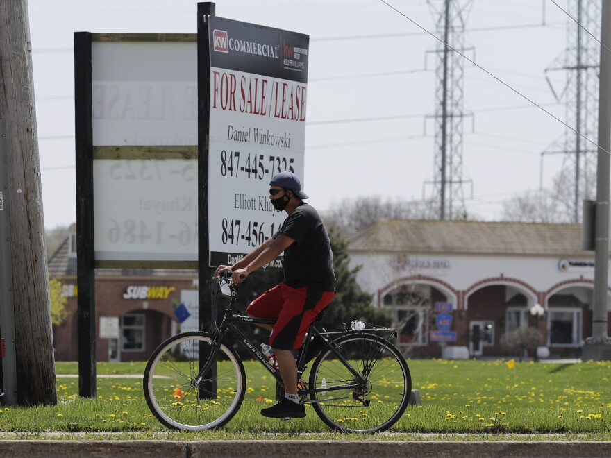 A man rides his bicycle in Gurnee, Ill., this past weekend. Officials say safe practices against the coronavirus need to continue if the state is to be successful with its phased reopening plan.
